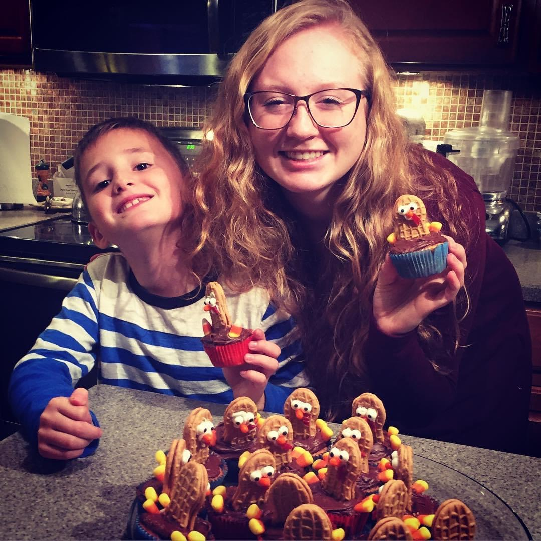 A young woman and boy holdingNutter Butter Turkey Cupcakes