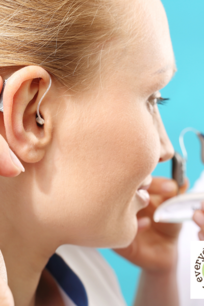 woman touching hearing aid behind ear