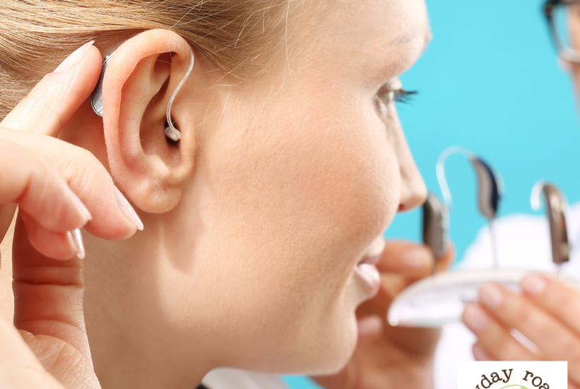 woman touching hearing aid behind ear